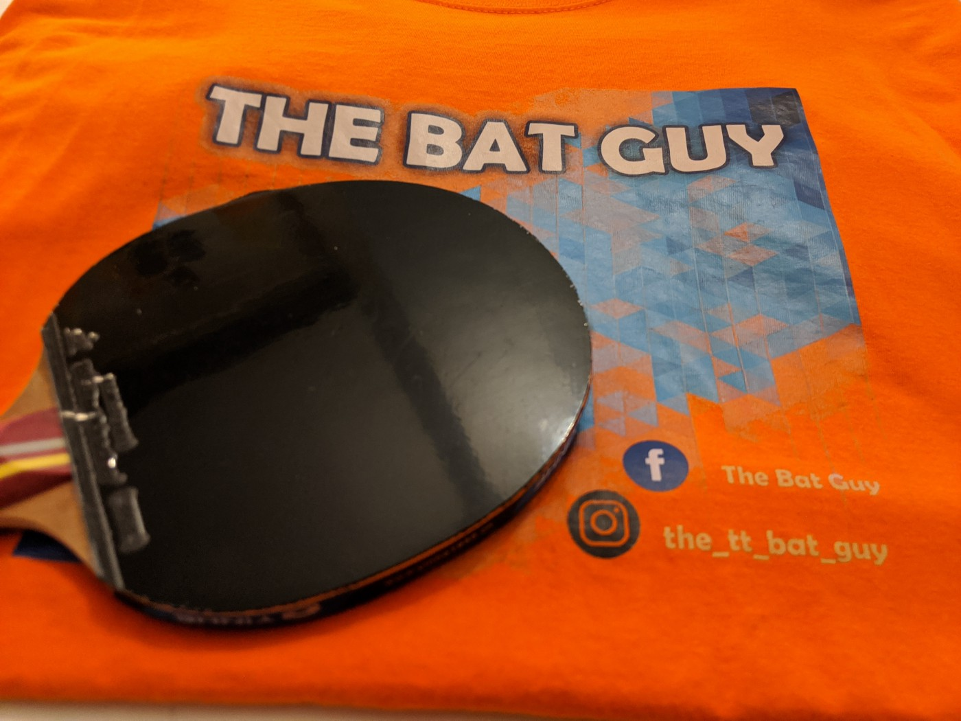 A 'The Bat Guy' branded orange shirt with a table tennis bat laid on top of it
