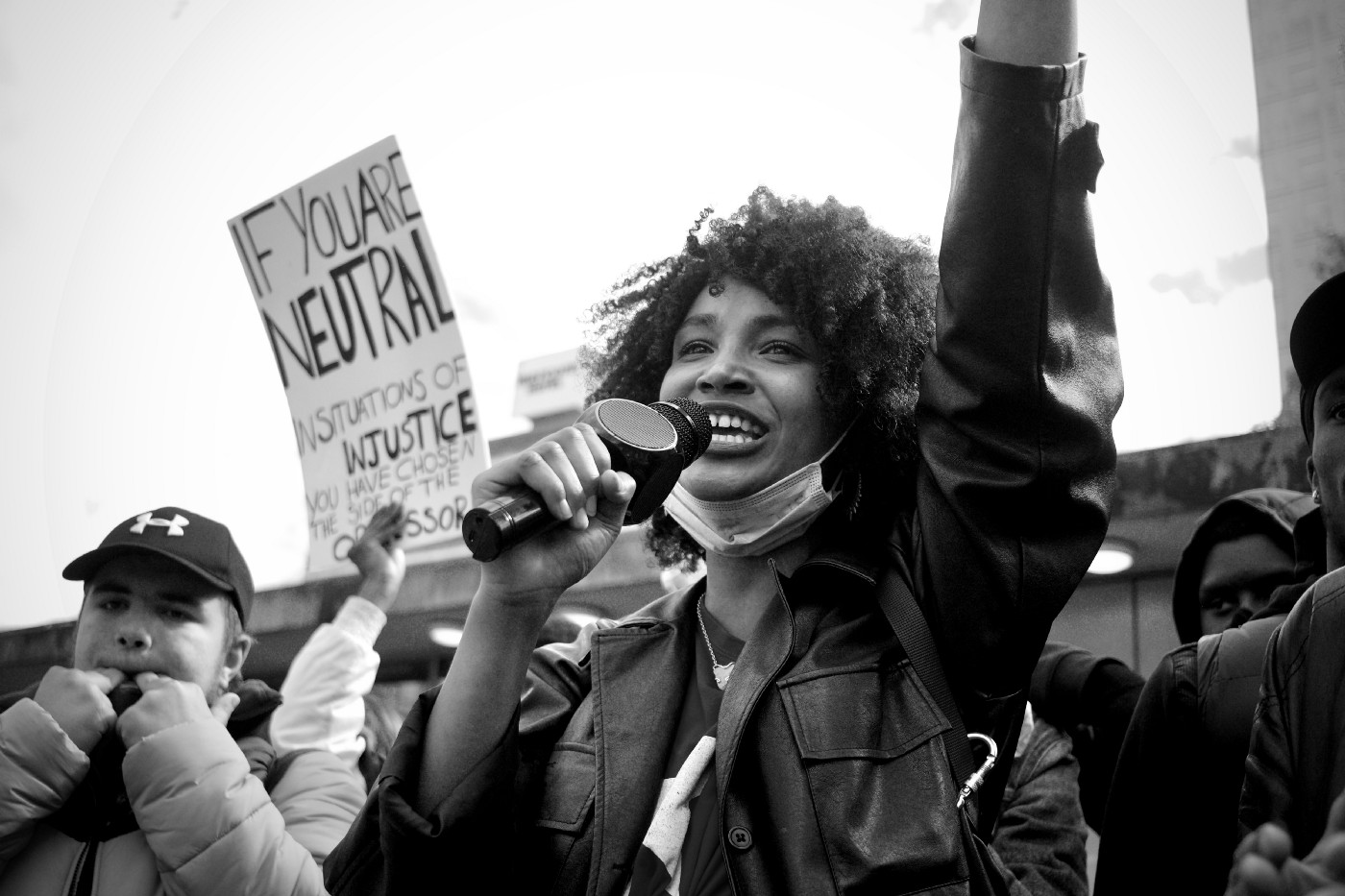 Black and white photo of a Black woman speaking into a microphone at a protest.