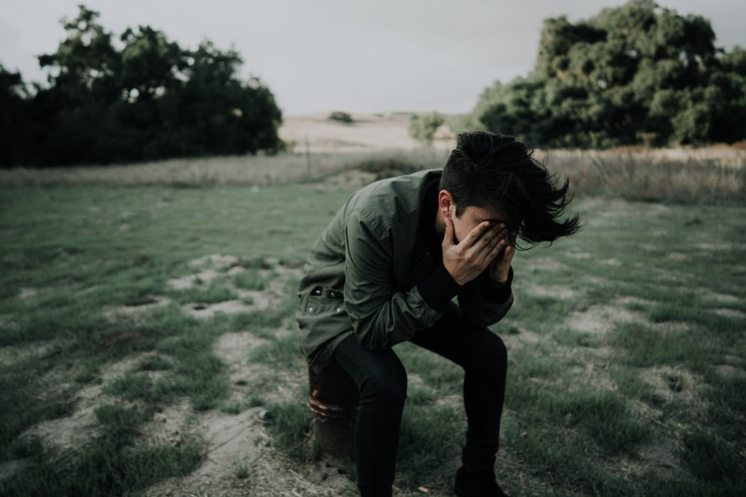 Sad young boy in dark green jacket and black pants hiding his face and slumped over on a barren farm field