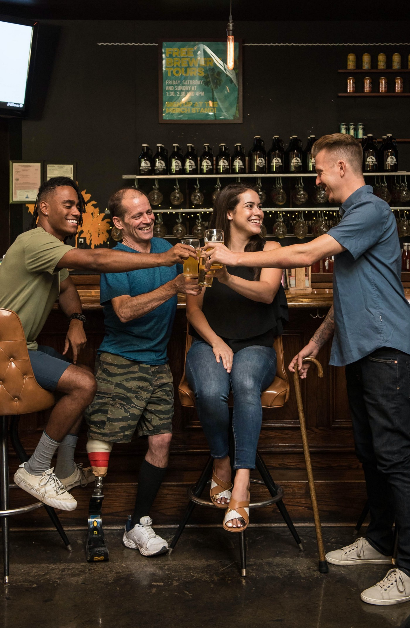 Four People Smiling Holding Glasses with Drinks. A bar is behind them. One holds a can while standing. The other standing person has a prosthetic leg.