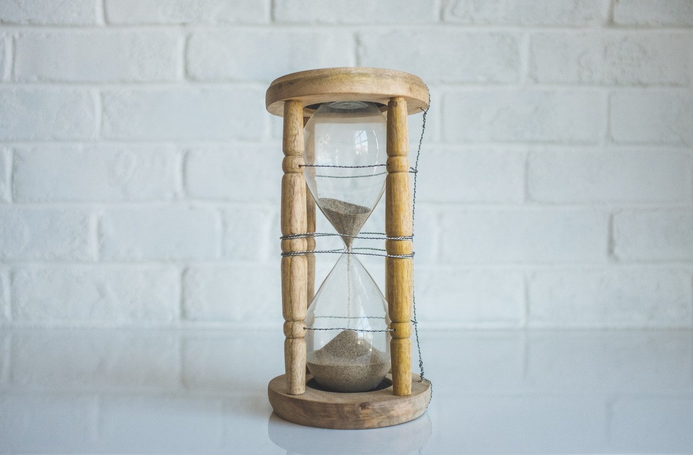 Wooden hourglass on a counter against a white brick wall