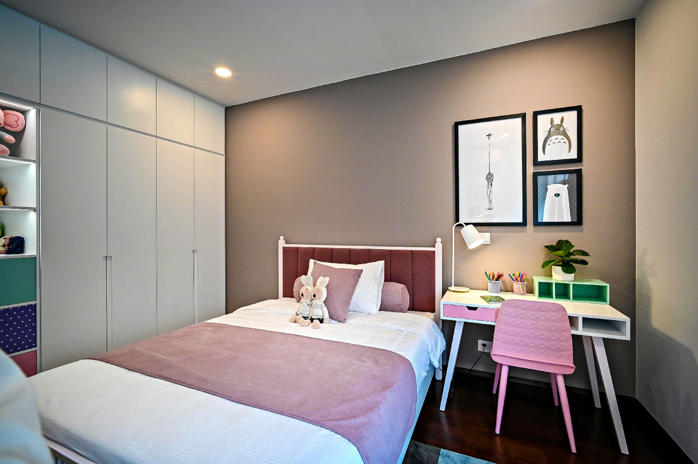 A very tidy, small, child's room (probably a girl's). There is a pink chair at the desk and two plush rabbits sit against the pillow on the bed which has a pink blanket and pink headboard.