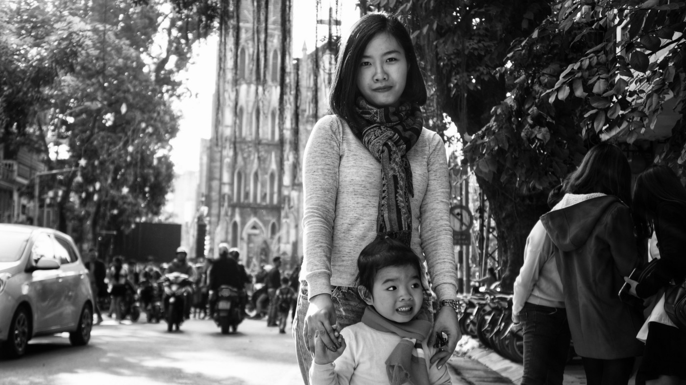 A black and white photo of a Vietnamese mom and daughter standing in a street.