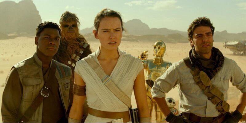 Boyega, Ridley, Isaac, and others looking concerned into the distance, with a mountainous desert around them.