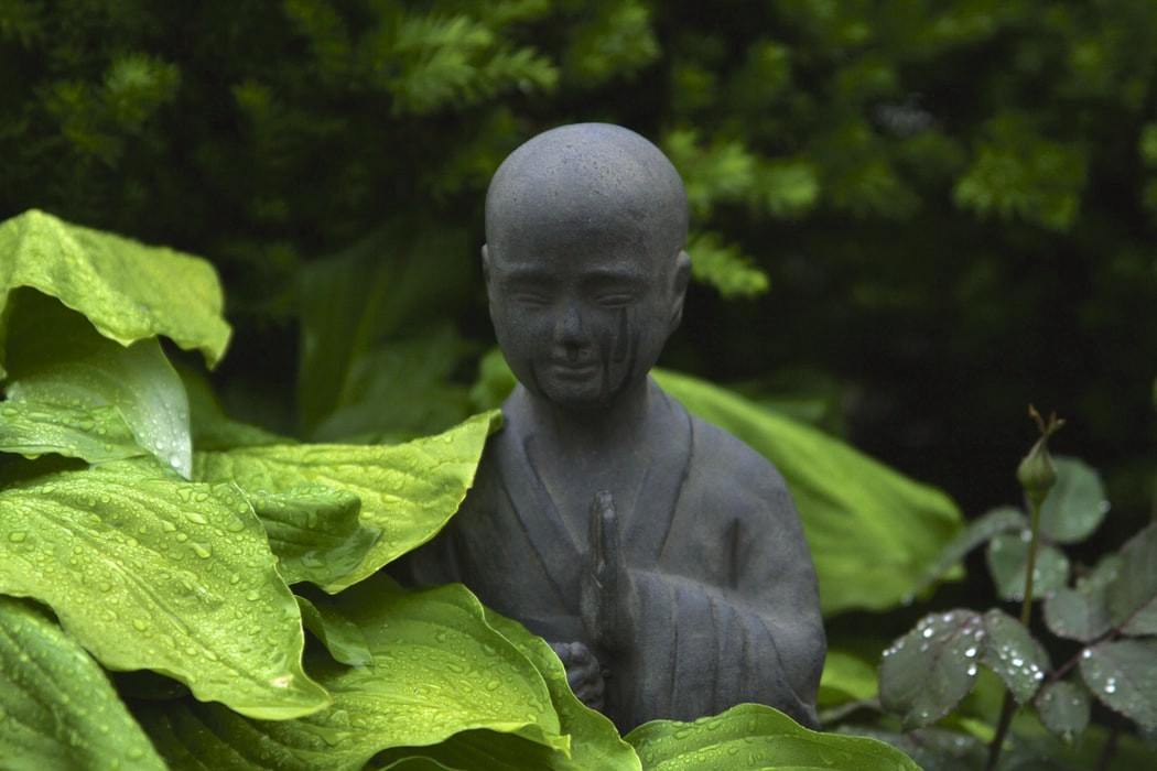 A Zen monk statue surrounded by plants