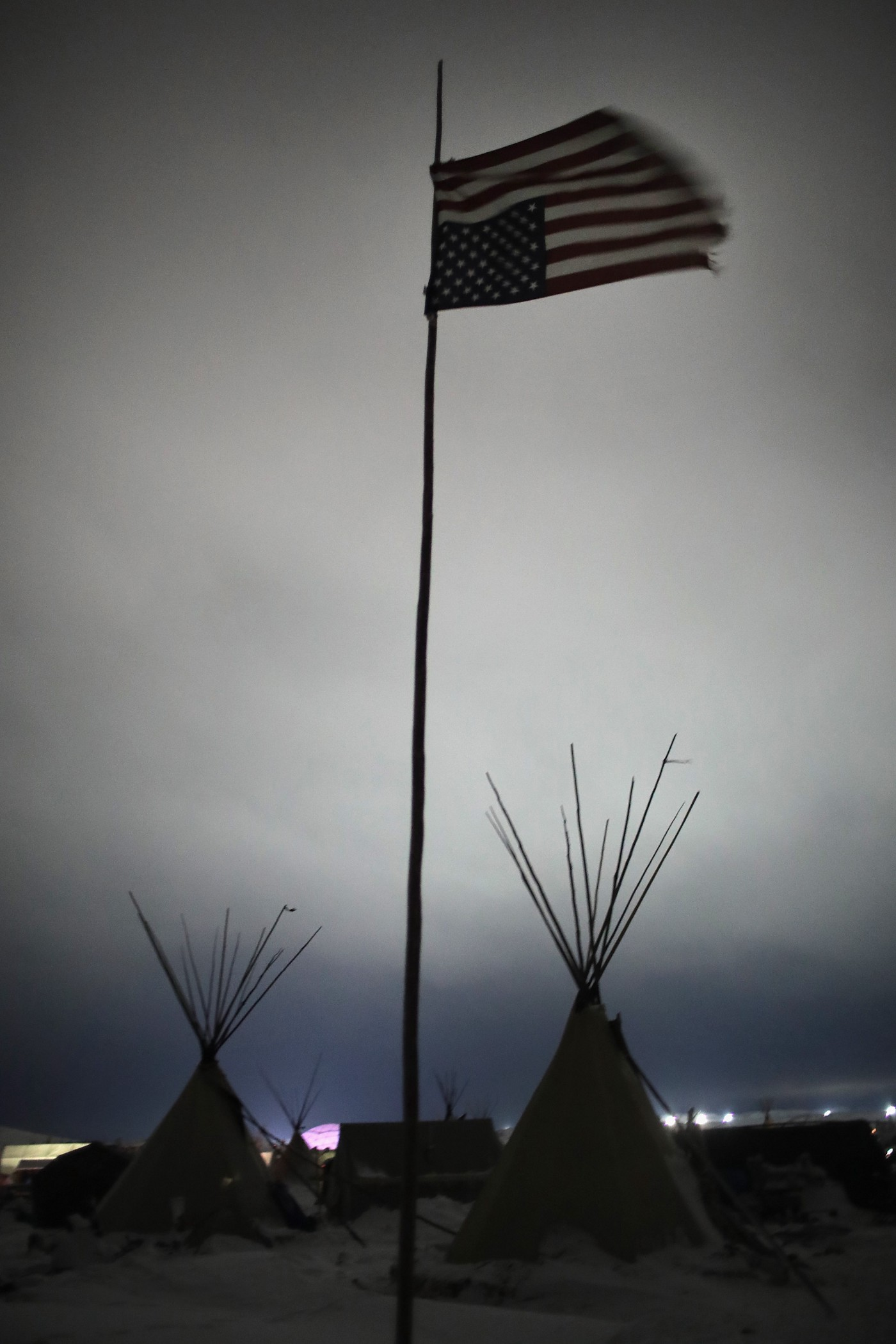 A photo of an upside down American flag hanging over a dark, ominous sky in Oceti Sakowin Camp.