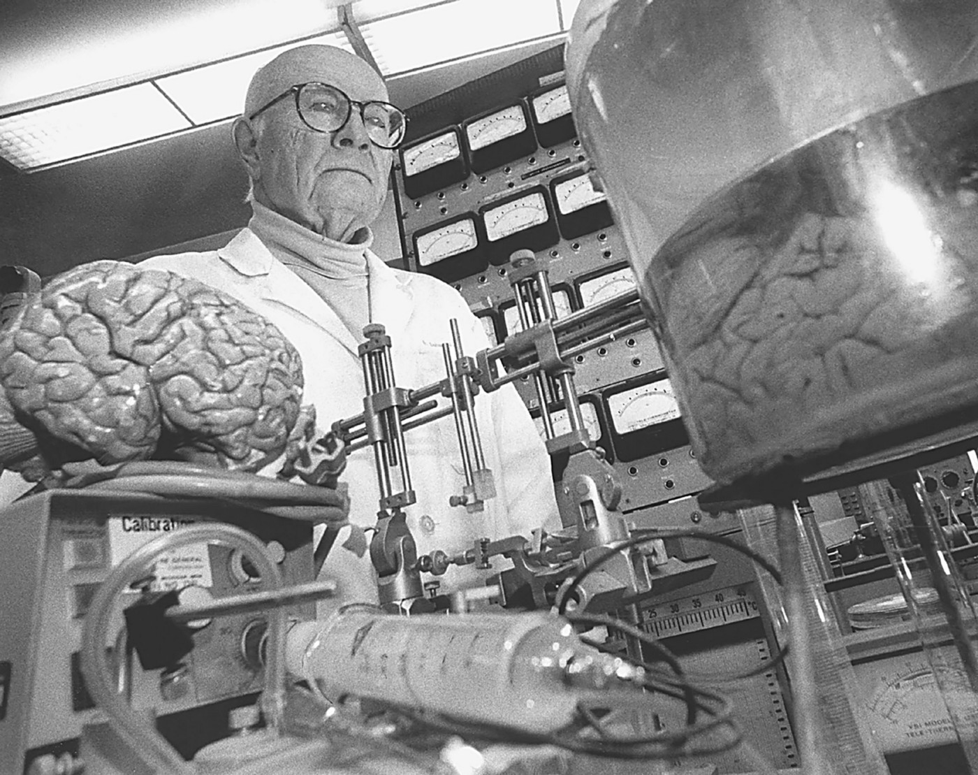 Dr. Robert White standing behind medical equipment and a brain in a jar