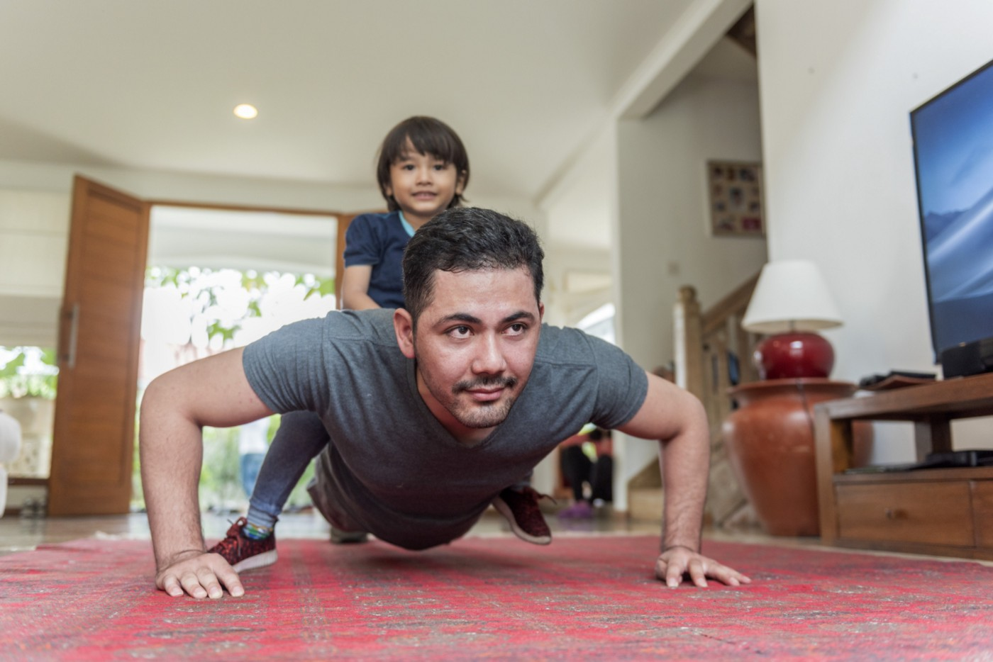 A photo of a father doing push ups in the living room while his son sits on his back.