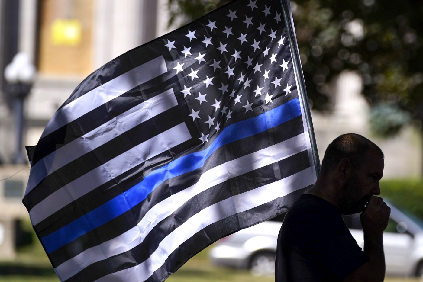 Person carrying the black American flag supposedly showing support for police
