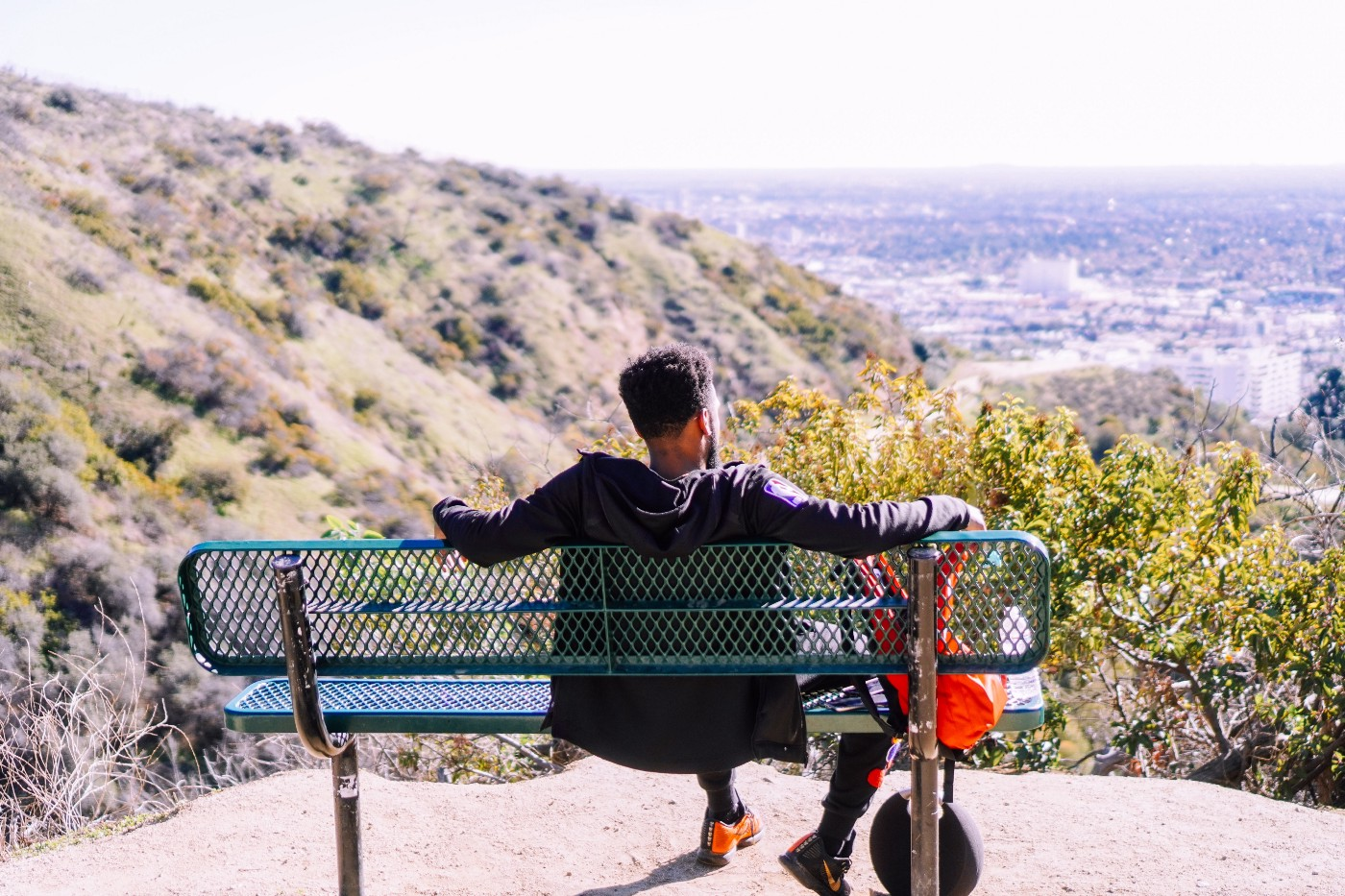 A man sitting on a bench looking out over a vista.