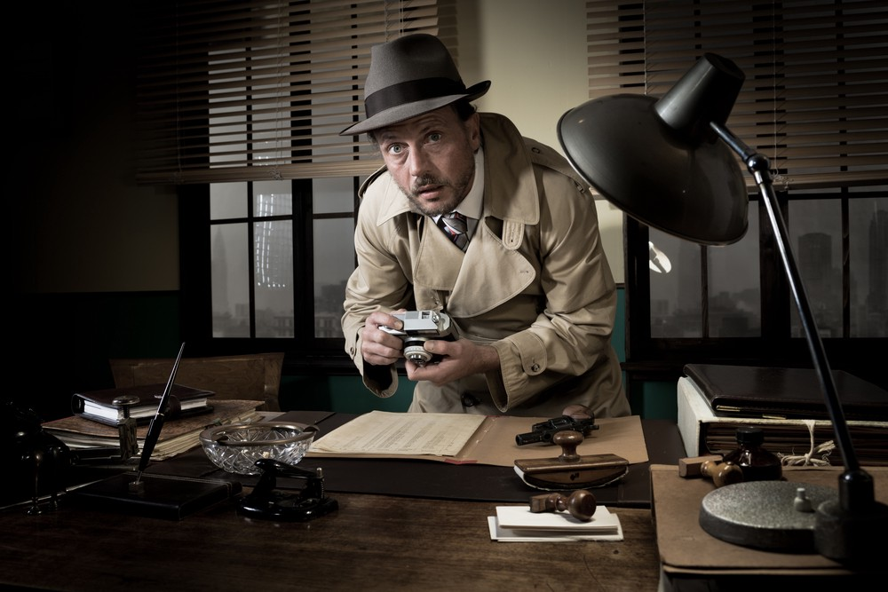 Image of a old-fashion spy taking pictures of files at a desk—a metaphor for electronic employee surveillance software