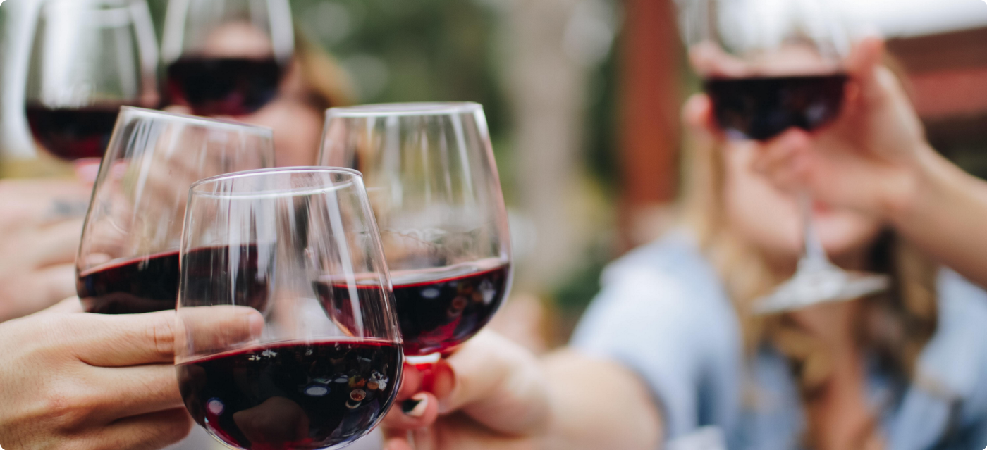A photograph of five glasses of red wine being clinked together in celebration