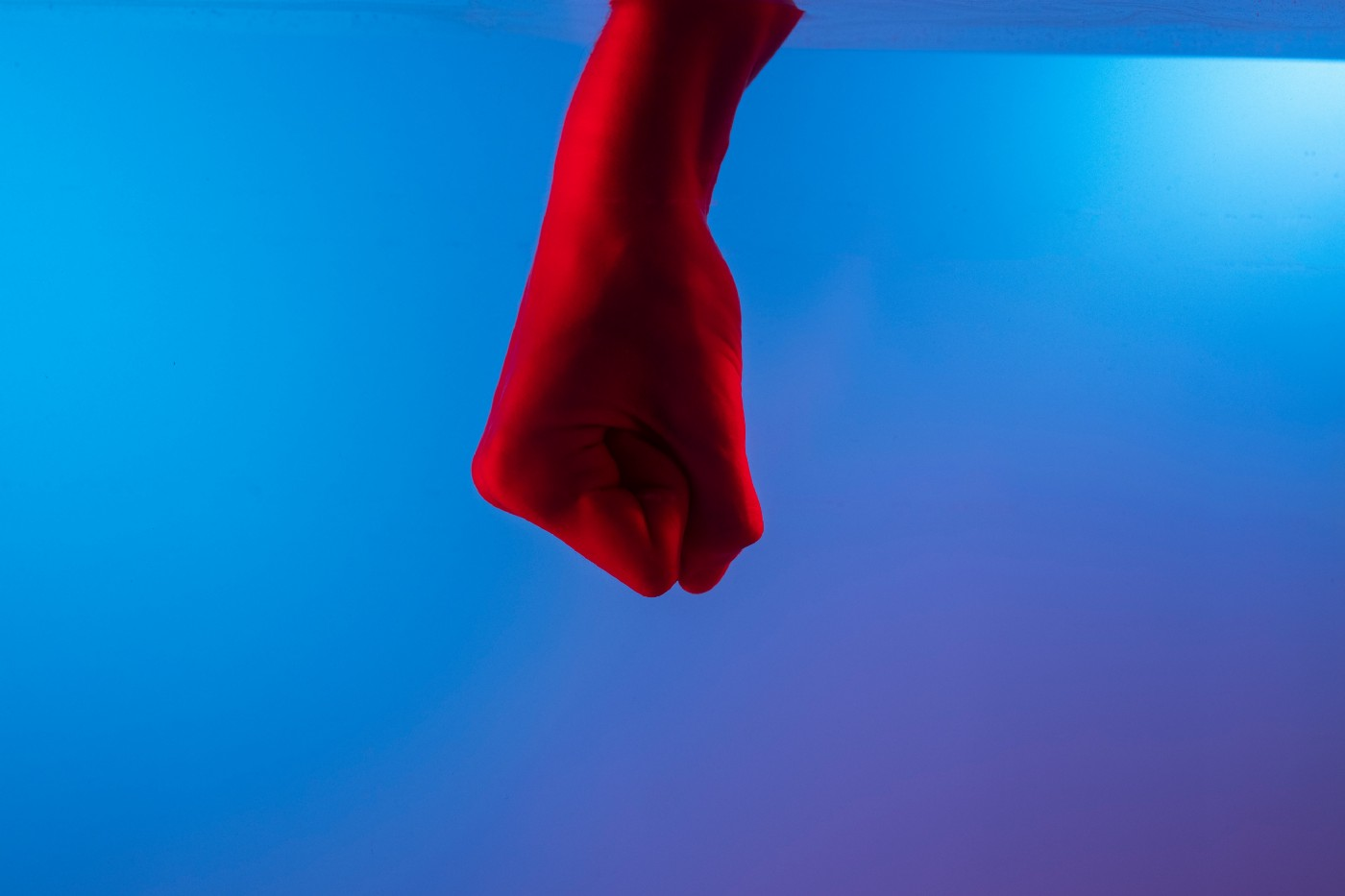 A fist bathed in red light in front of a blue background.