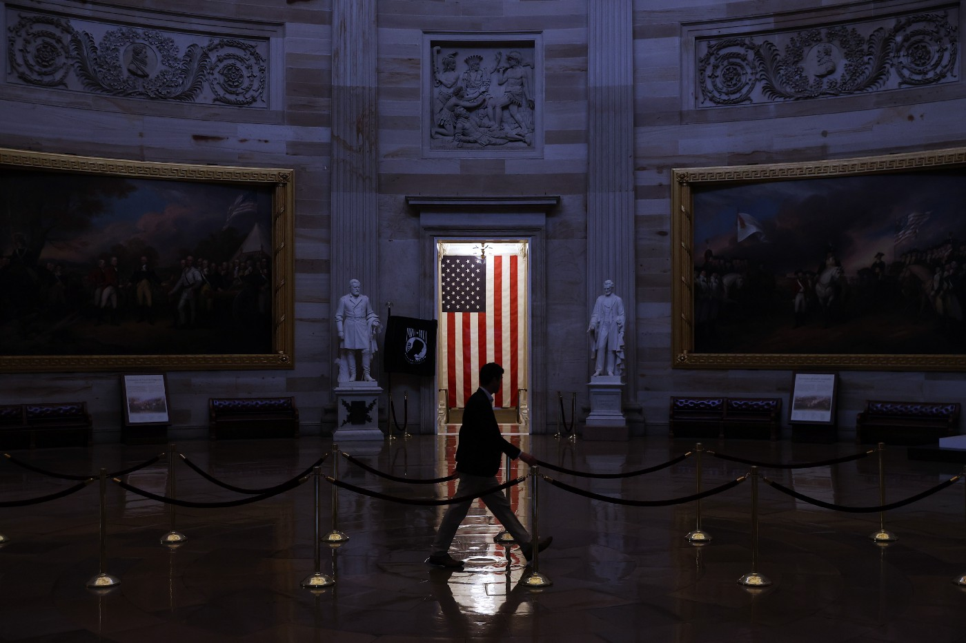 A man walks through the U.S. Capitol Rotunda, empty of tourists as only essential staff and journalists are allowed to work.
