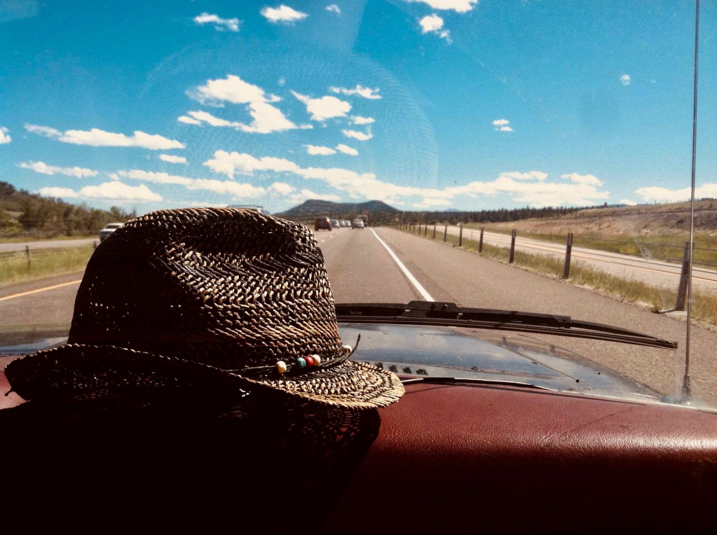 Straw hat resting on the dashboard of a car rolling on a road, sunny day blue skies.