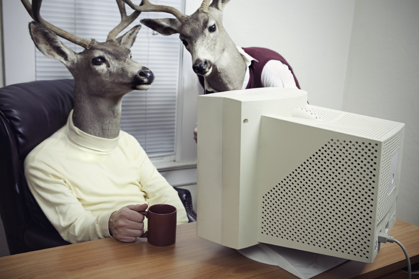 Two deer people learning how to code on an old computer