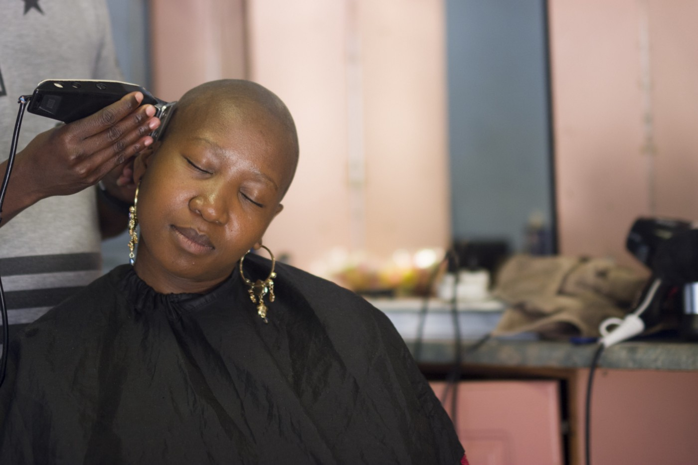 Black woman shaving her hair, with a peaceful expression.