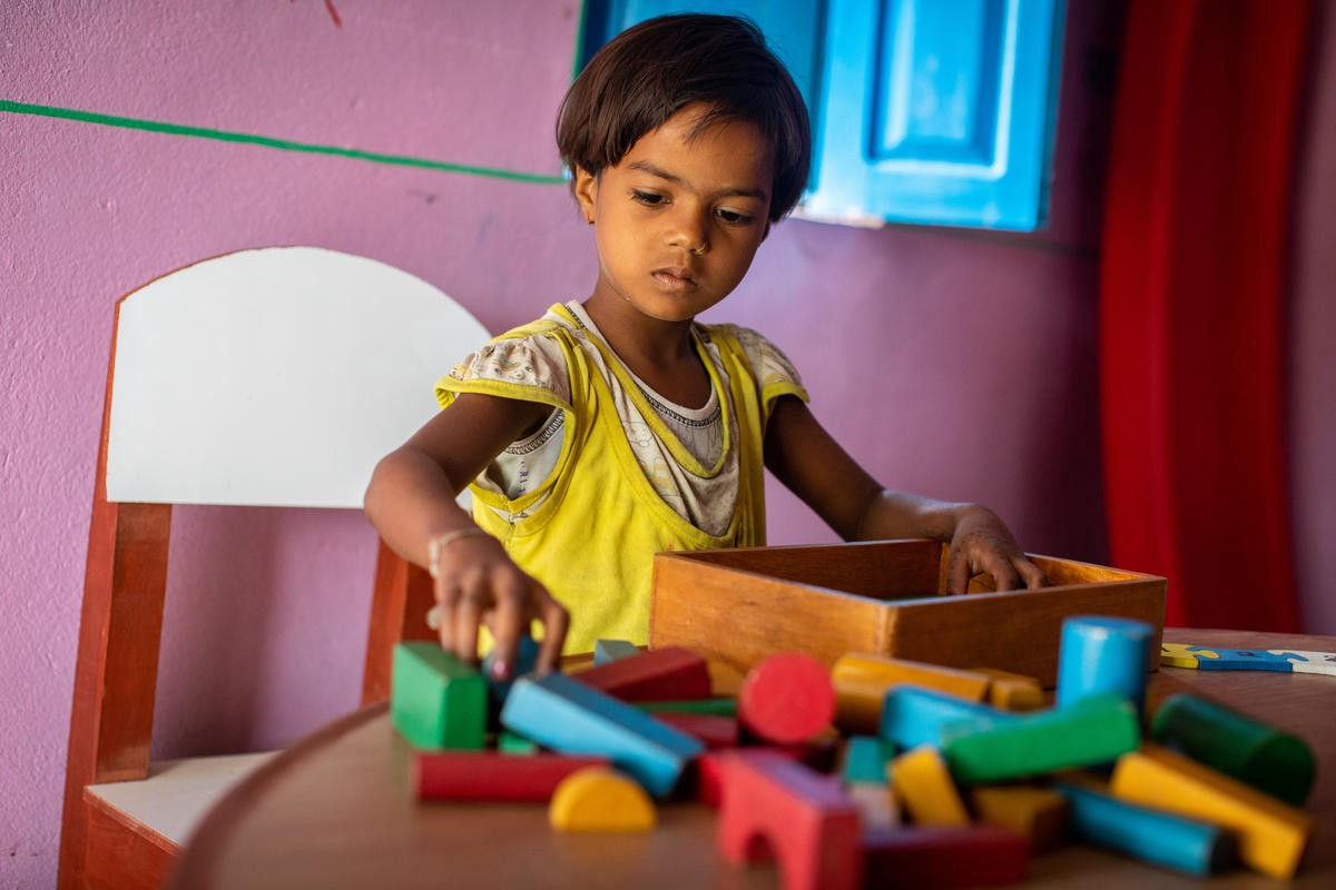 A child plays with wooden blocks while sitting on a small chair at a wooden table.
