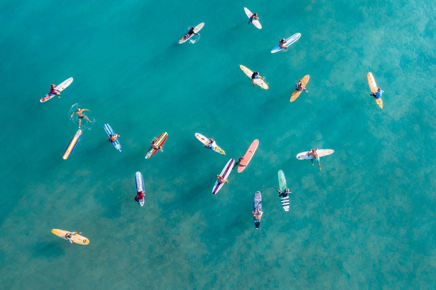 An arial view of surfers floating on a calm blue sea.