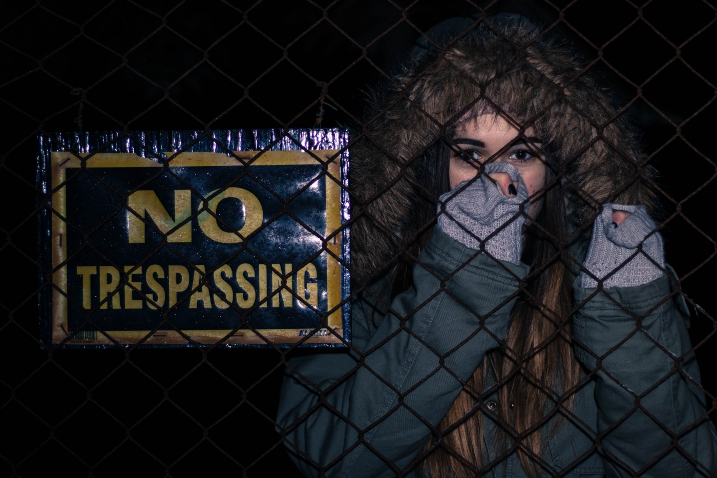 woman, afraid, standing behind fence with NO TRESPASSING sign