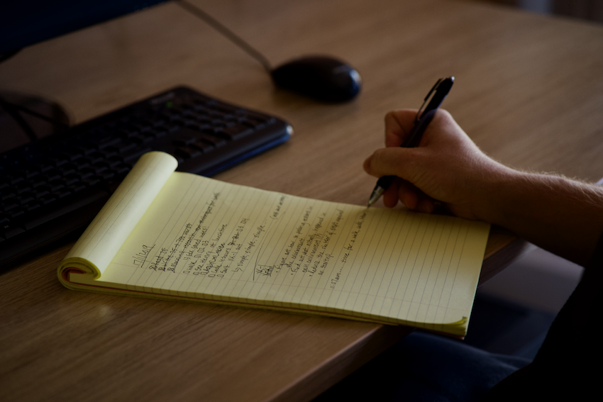 lined paper with writing on it, pen being held by hand writing on the paper