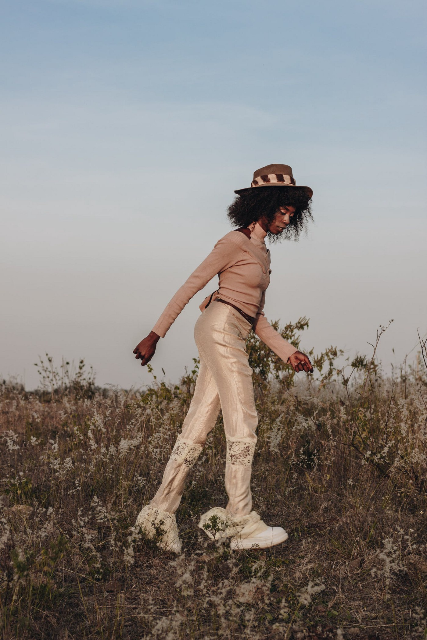 A fashionable woman walking in a serene and uphill place.