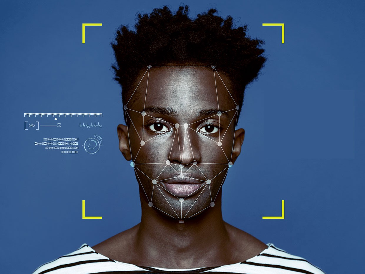 A dark-skinned person stares directly at the screen with facial recognition mapping points symmetrically placed around their face.