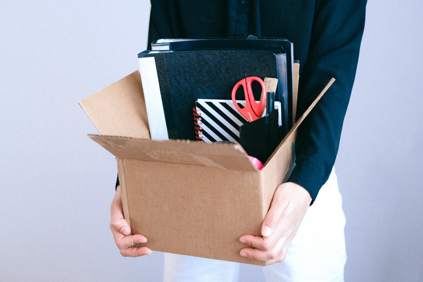 Torso of a female in white slacks and a navy shirt holding a cardboard box full of office supplies