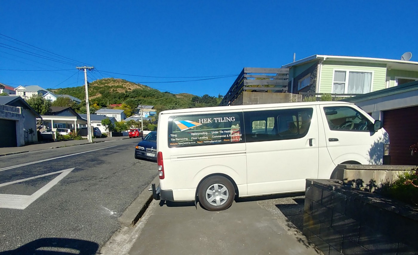 A white van parks completely across a footpath.