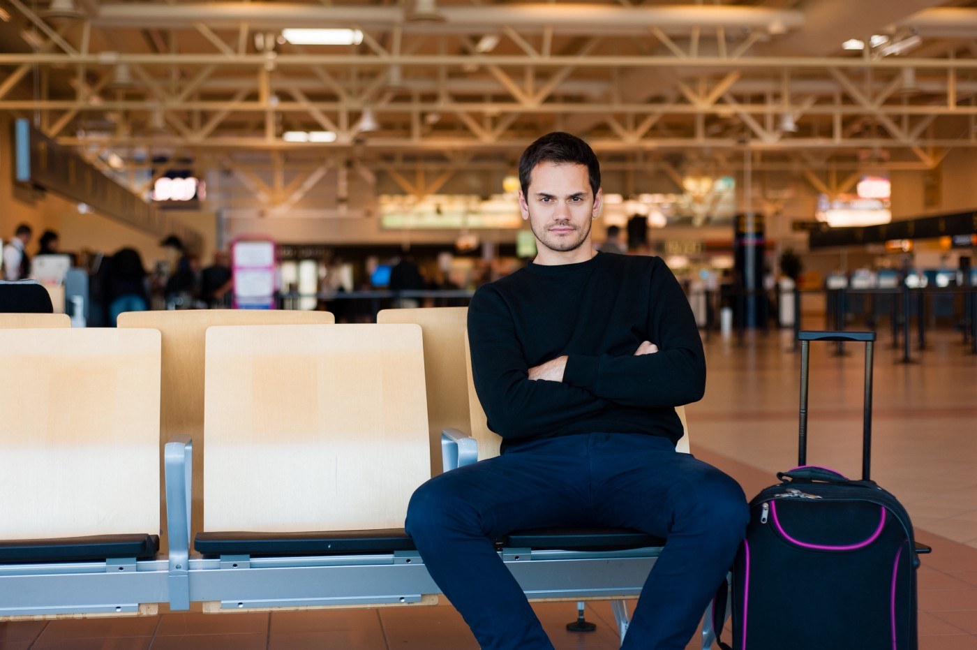 Portrait of handsome smiling man in casual wear sitting in the hall of the airport terminal, while waiting for his flight.