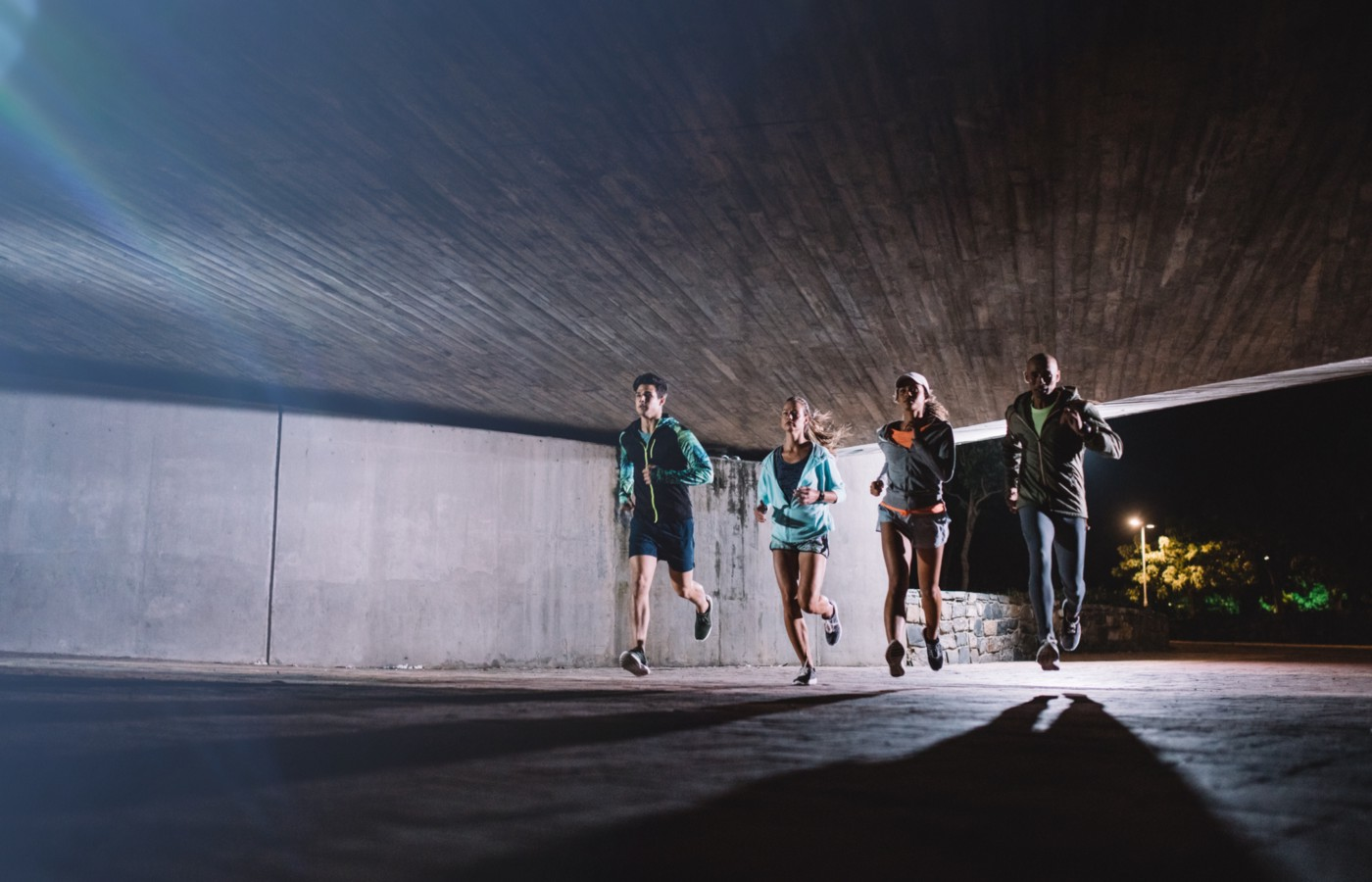 Four people jogging under an overpass