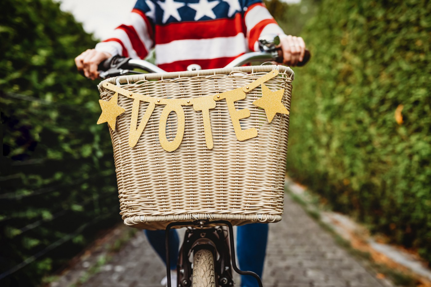 "Person riding bicycle with ""VOTE"" banner on it."