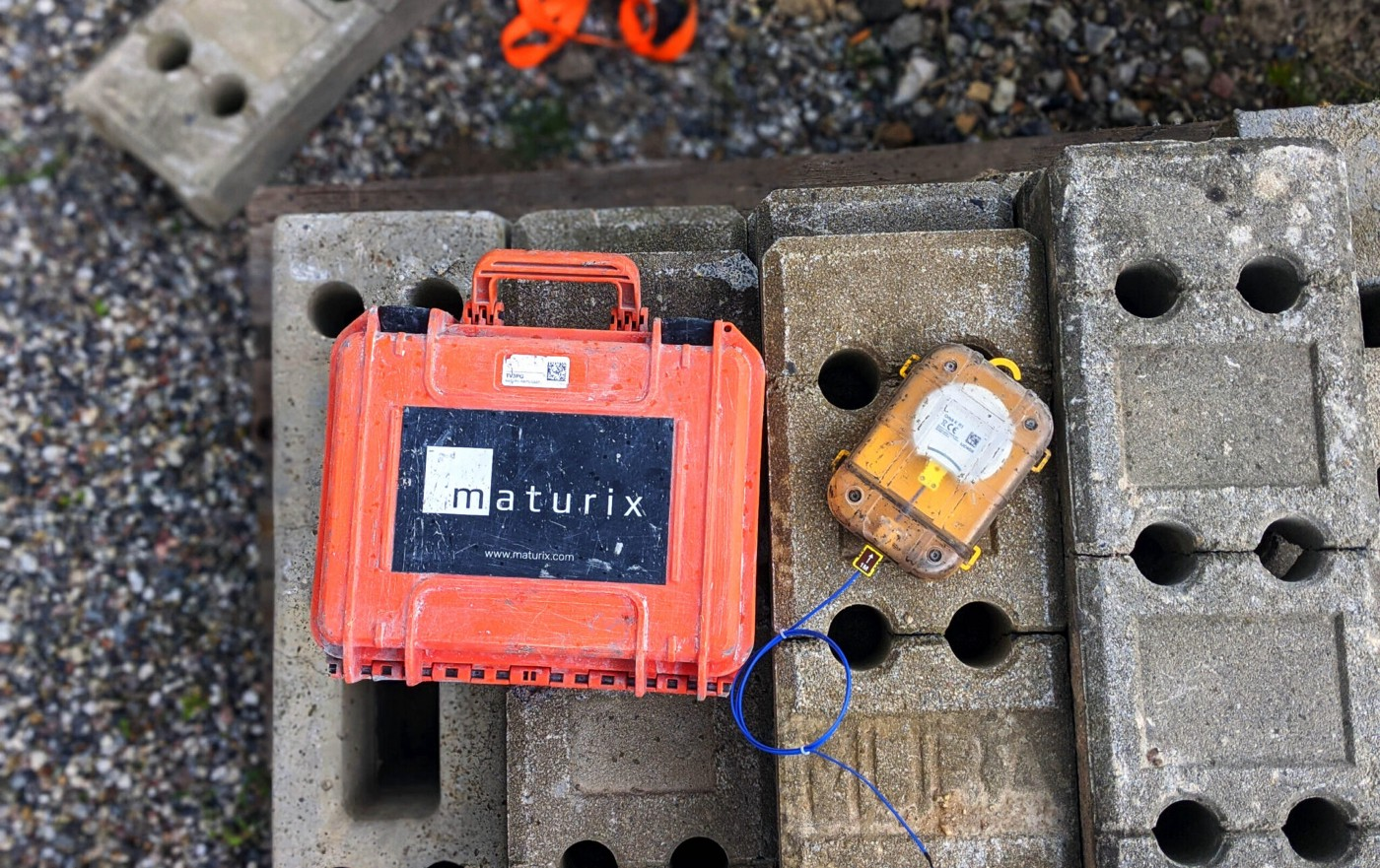 A Maturix Sensor and its case are laying next to each other on concrete blocks in a worksite.