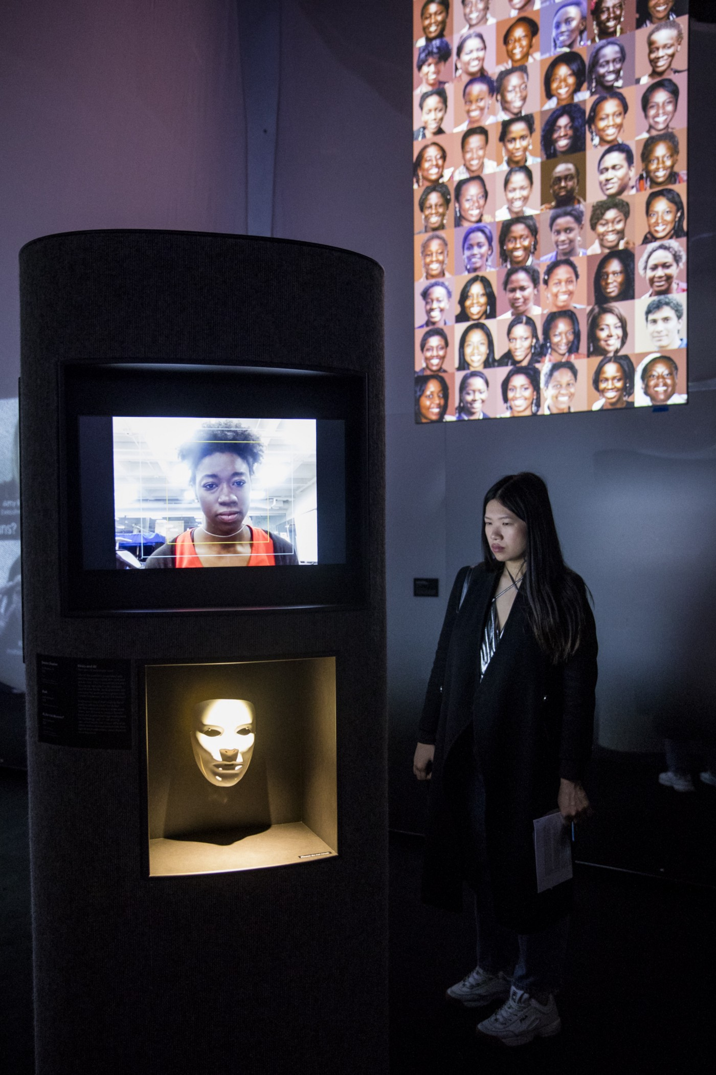 A tall, dark oblong cylindrical plinth containing two niches displaying a video of Joy Buolamwini along with a white mask.