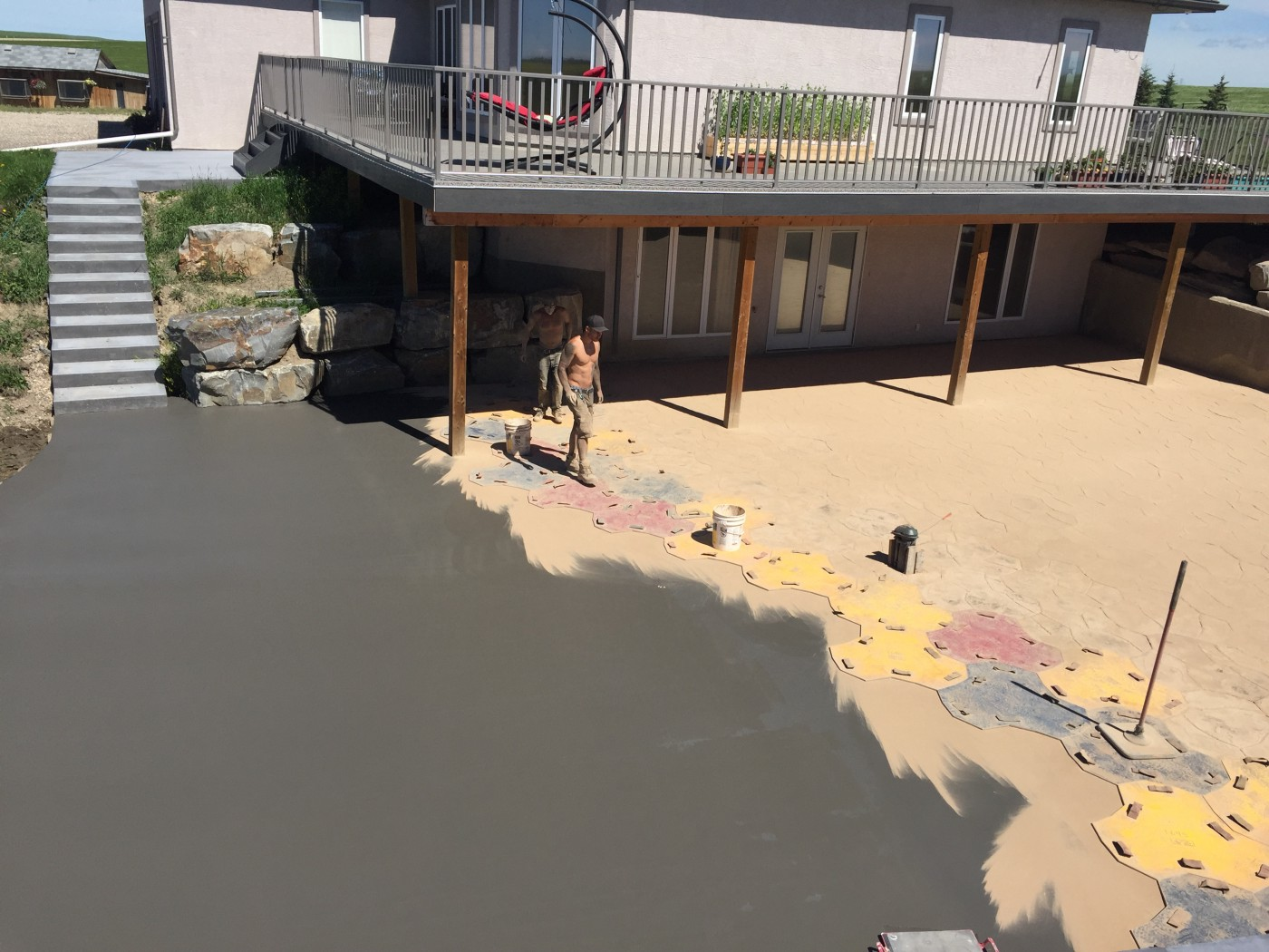 A stamped concrete patio being finished. A worker stands on mats that impression the wet concrete with a pattern.