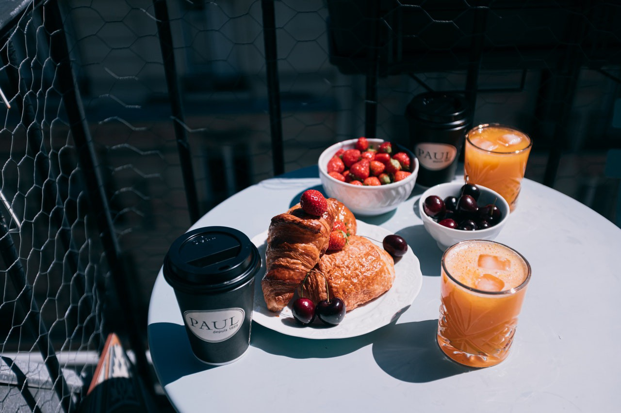 a table outside with breakfast, orange juice, coffee, croisants and fruits