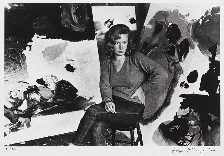 Photograph of woman with brown hair, jumper and jeans sitting in front of art