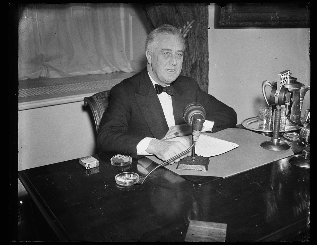 President Franklin D. Roosevelt sitting at desk, giving radio address.