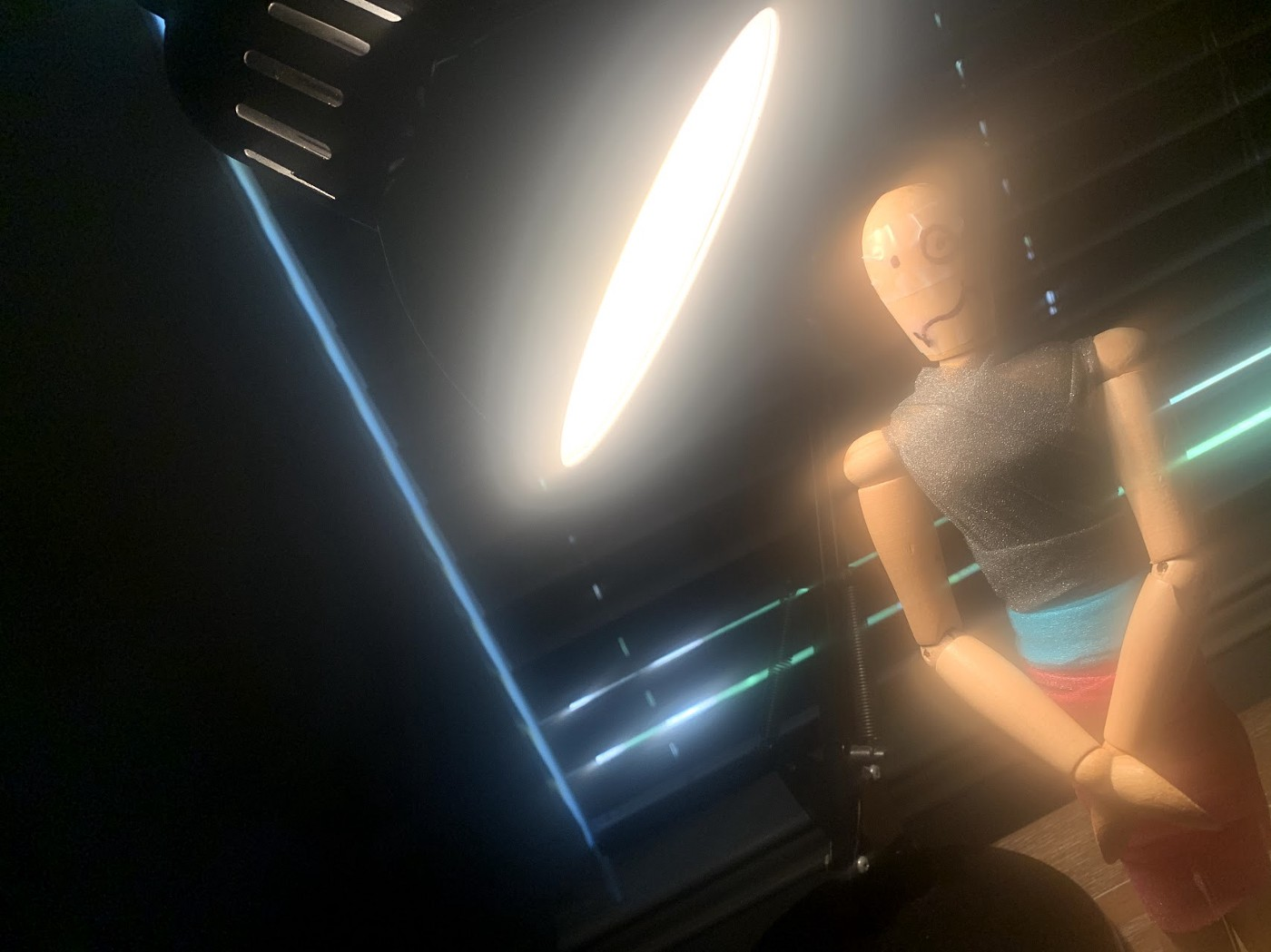 Mannequin stands with hands in from of body while a lamp shines over her from the left side.