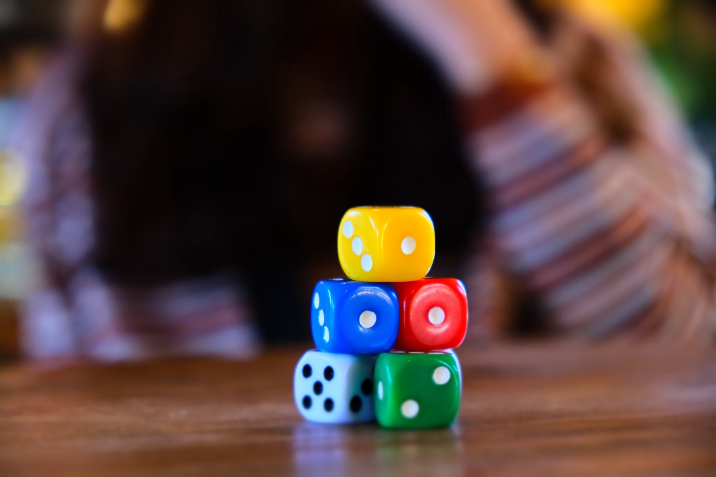 A stack of dice or a board game sitting on a table with a person behind them.
