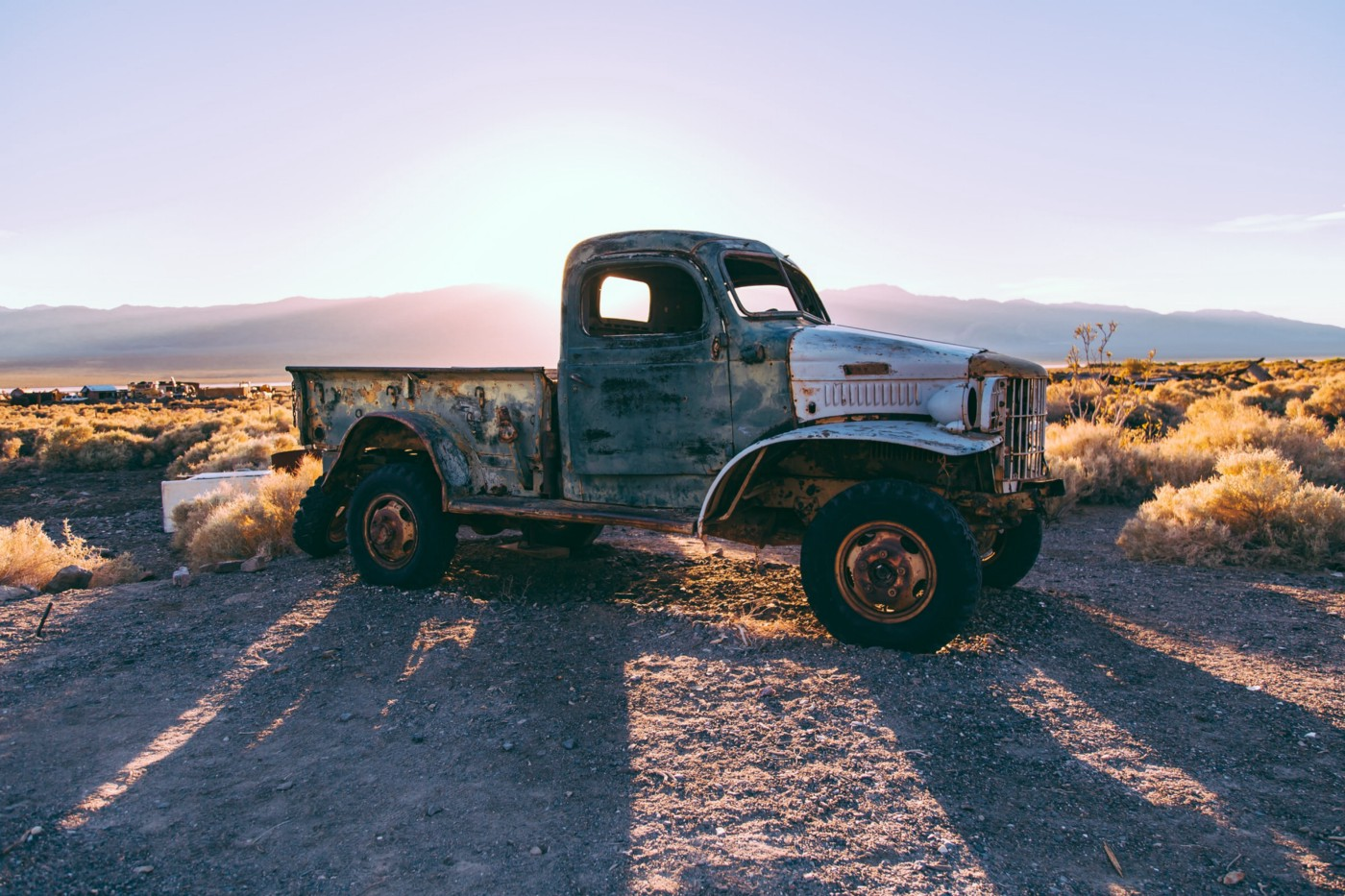An old style grey single cab truck on scrub land with the low sun behind casting a long shadow.