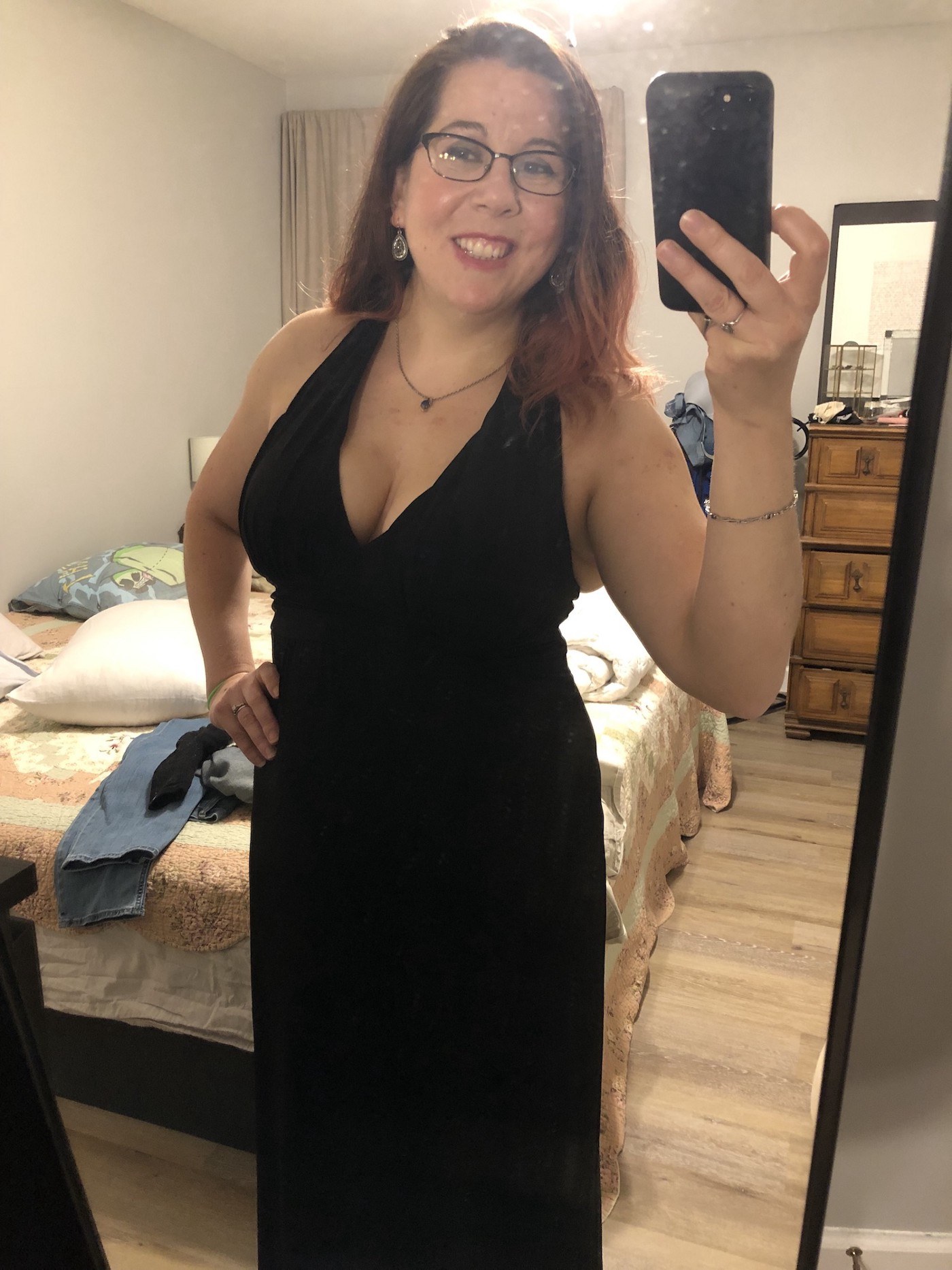 The author, dressed in a black, floor length, v neck dress, with one hand on her hip taking a mirror selfie, and not realizing that there is a pair of jeans on the bed. She is smiling and proud of her 100 Burpee accomplishment that day.