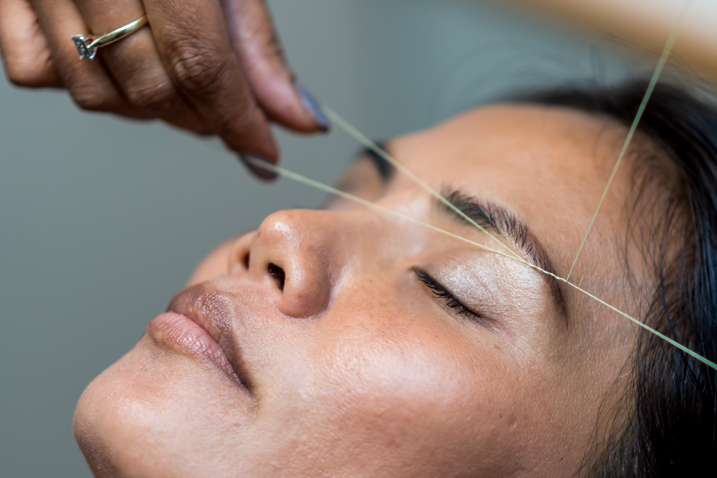 Woman lying down while her eyebrows are threaded.
