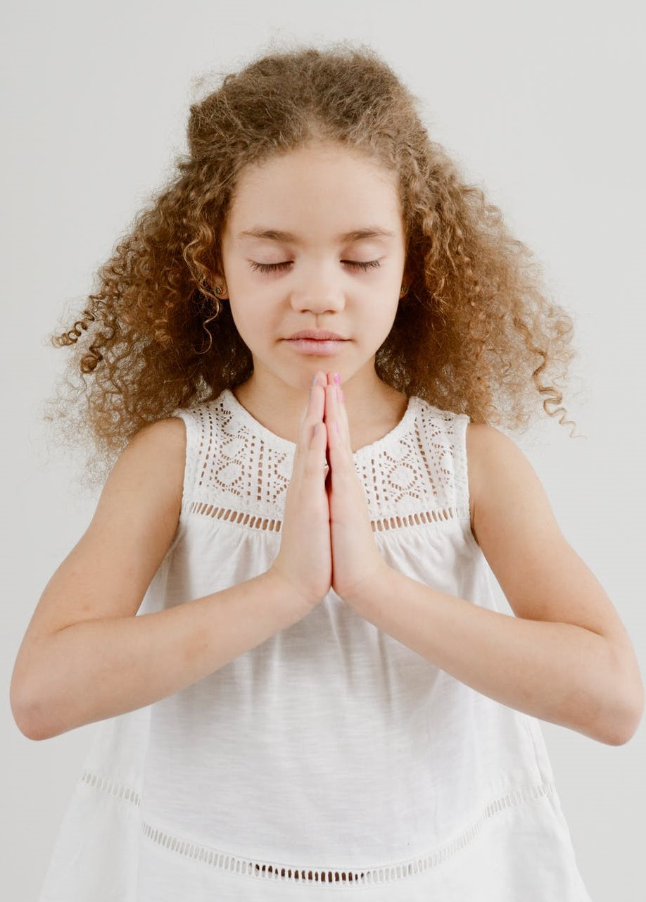 """Photo of a young girl with curly hair, eyes closed and hands in """"namaste"""" pose"""