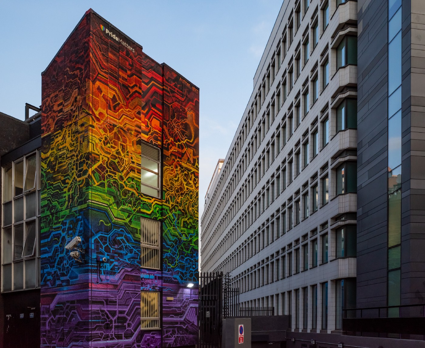 """Rainbow colored """"Pride Matters"""" mural on the side of a building in a city"""
