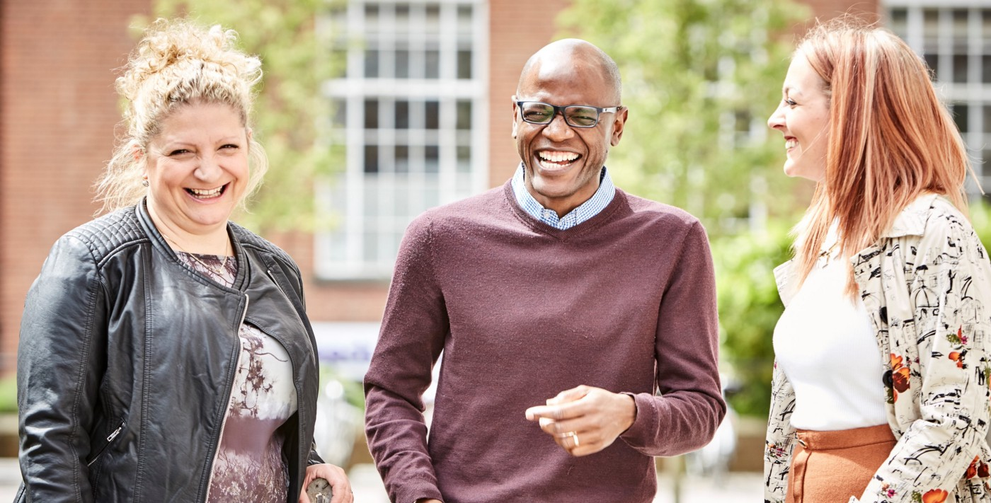 Three mature students—two white women stand either side of a black man who is wearing glasses—laugh together on a university campus.