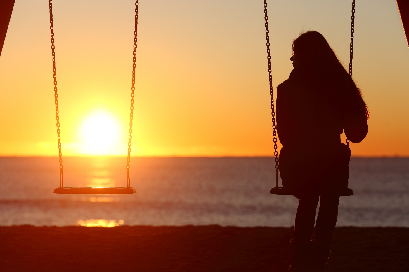Woman staring at the sunset on a beach on a pair of swings with one swing empty