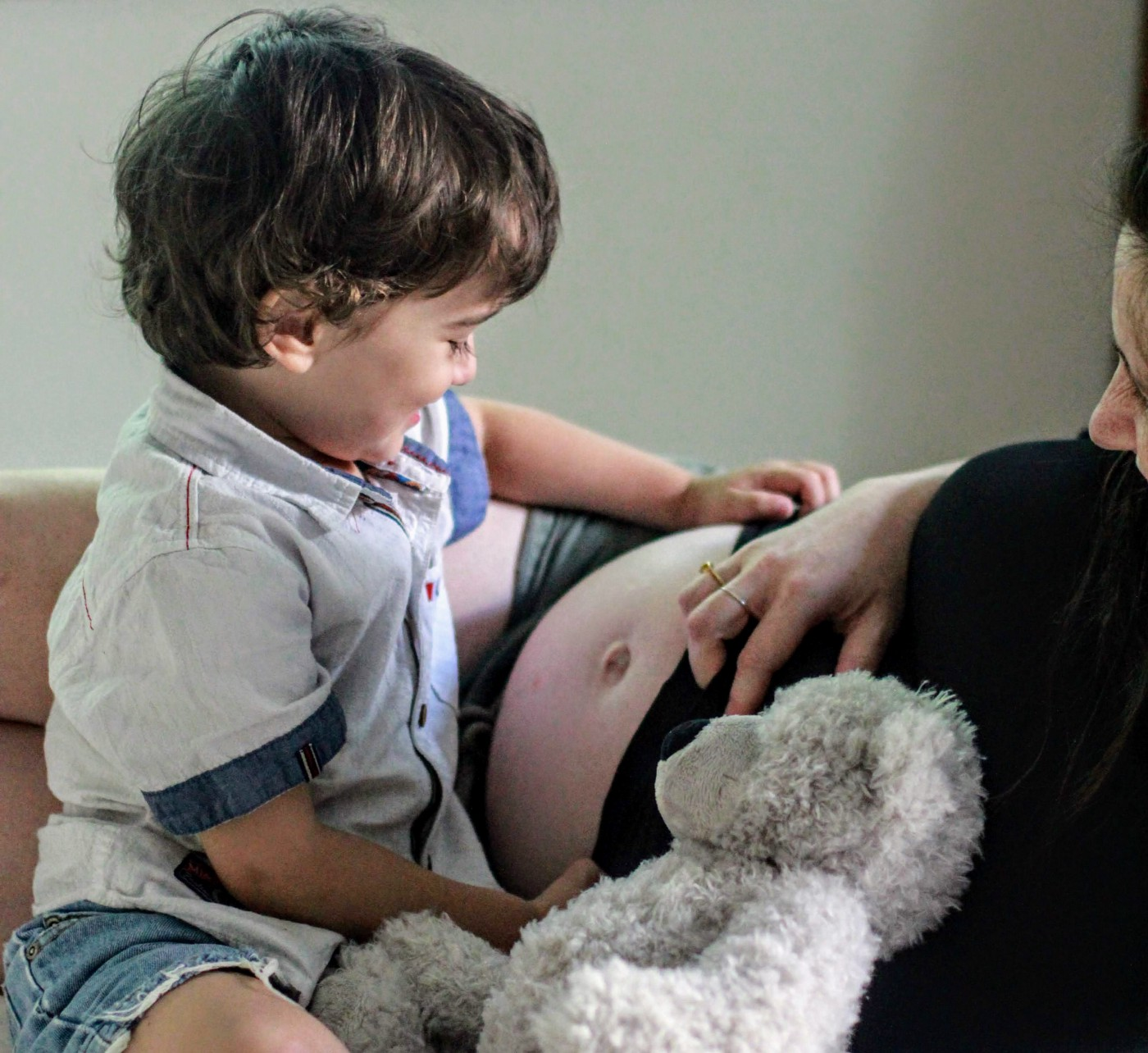Toddler with brown hair admires the pregnant belly of his mother, who is lying reclined.