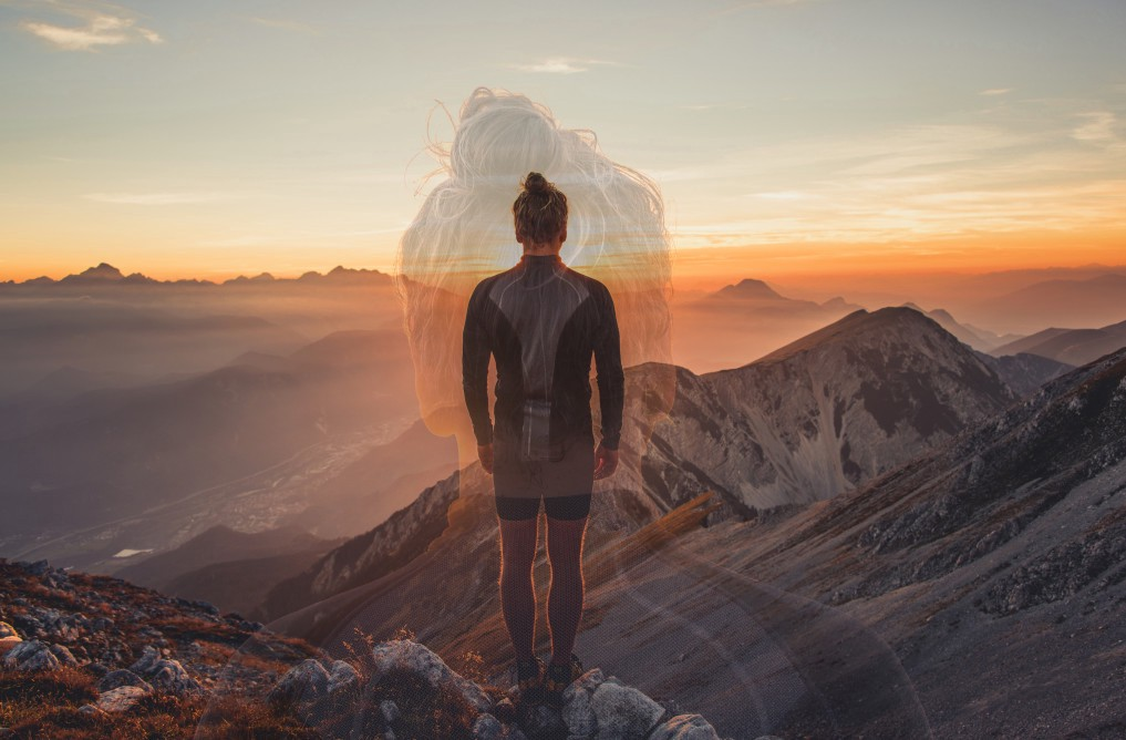 A hiker observing the sunset at the top of a big mountain