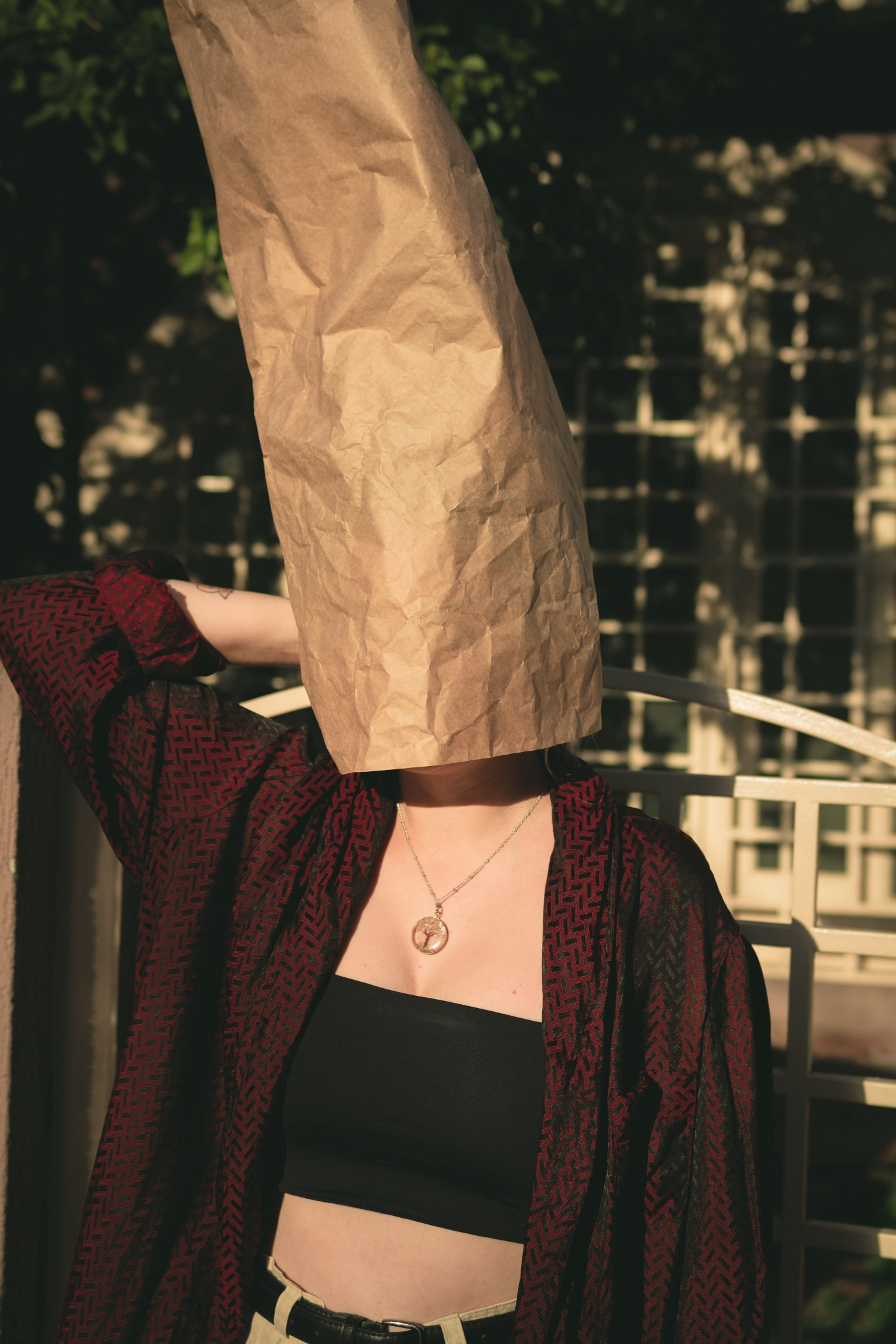 Woman with a paper bag over her head.